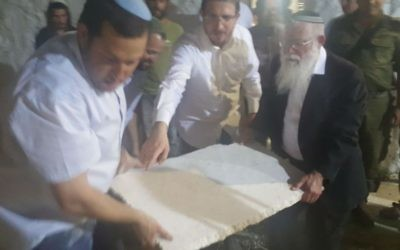 Samaria Regional Council head Yossi Dagan (L) carries a large stone slab with Samaria Regional Council rabbi Elyakim Levanon at Joseph's tomb in Nablus on May 10, 2017. (Courtesy: Samaria Regional Council)
