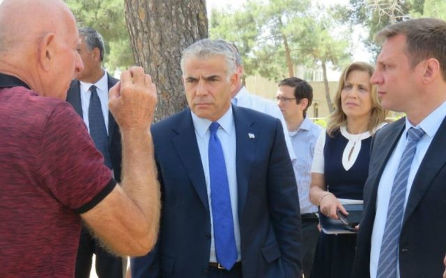 Yesh Atid leader MK Yair Lapid, center, flanked by MKs Aliza Lavie, second right, and Yoel Razvozov, right, at Jerusalem's Ammunition Hill, May 15, 2017. (Courtesy)