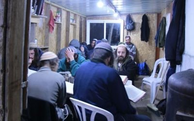 Yeshivat Homesh students pictured in their study hall that lies on top of the evacuated settlement of Homesh. The makeshift building was burned down in an apparent arson attack. (Courtesy: Yeshivat Homesh)