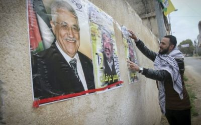 A Palestinian hangs a poster depicting late Palestinian leader Yasser Arafat and Palestinian Authority President Mahmoud Abbas, in the West Bank city of Nablus, March 14, 2017. (Nasser Ishtayeh/Flash90