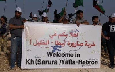 Activists hold the sign that was placed at the entrance of the Sumud Freedom Camp in the South Hebron Hills. They claim the location to have been where a Palestinian village called Sarura was once located. (Credit: Rami Ben-Ari)