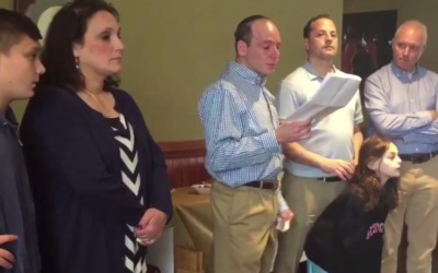(From L-R) Ruth Schwartz looks on as her husband Ari reads a speech in memory of their son Ezra at a Rutgers University ceremony posthumously making inducting him as a member on April 30, 2017. Standing next to Ari are former AEPi presidents Seth Greenfield and Seth Jonas. (Screen capture/USA Today)