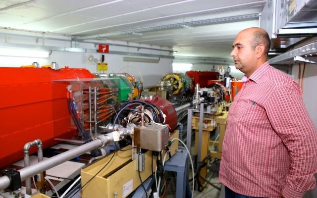 An employee from SESAME stands next to the particle accelerator in Allan, Jordan. (Sharing Knowledge Foundation)