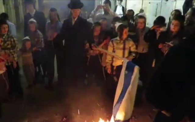 Ultra-orthodox Jews in the Jerusalem neighborhood of Mea Shearim burn an Israeli flag at the end of the country's 69th Independence Day, May 2, 2017. (Channel 10 screenshot.)