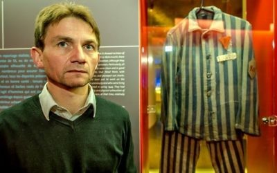 French historian Laurent Thiery poses near the camp clothes of a deportee forced to work at the underground weapon factory producing the Nazis' V2 rocket. (AFP/Philippe Huguen)