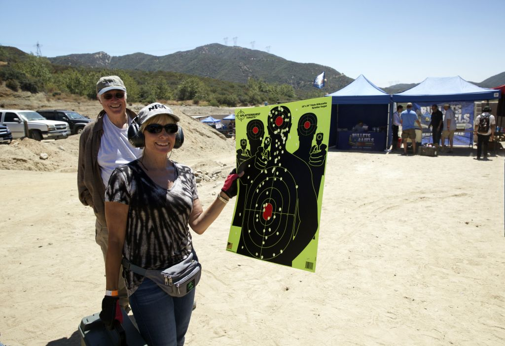 A proud shooter holds up her target at Bullets & Bagels. (Courtesy)