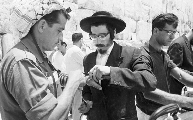 An ultra-orthodox man helps a soldier to lay Tefillin at the Western Wall, June 22, 1967. (From the collection of Dan Hadani, National Library of Israel).