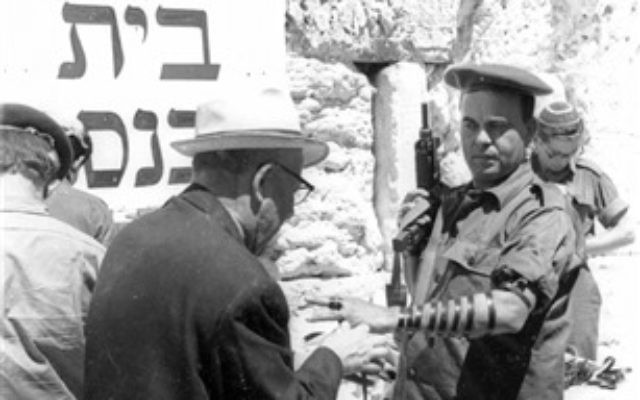 A soldier lays Tefillin at the Western Wall, June 11, 1967. (From the collection of Dan Hadani, National Library of Israel).