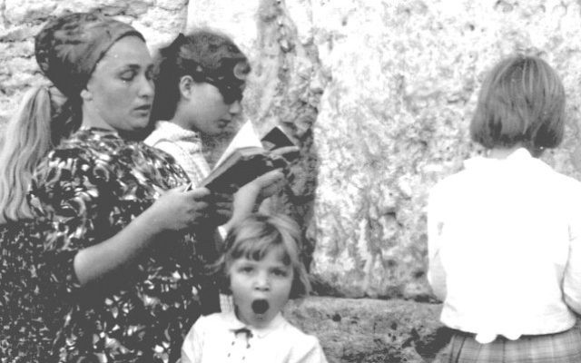 A mother and her daughters pray at the Western Wall, while the youngest girl yawns, June 17, 1967. (From the collection of Dan Hadani, National Library of Israel).