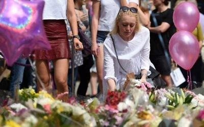 A woman places flowers in St Ann's Square in Manchester, northwest England on May 25, 2017, in tribute to the victims of the May 22 terror attack at the Manchester Arena. / AFP PHOTO / Oli SCARFF