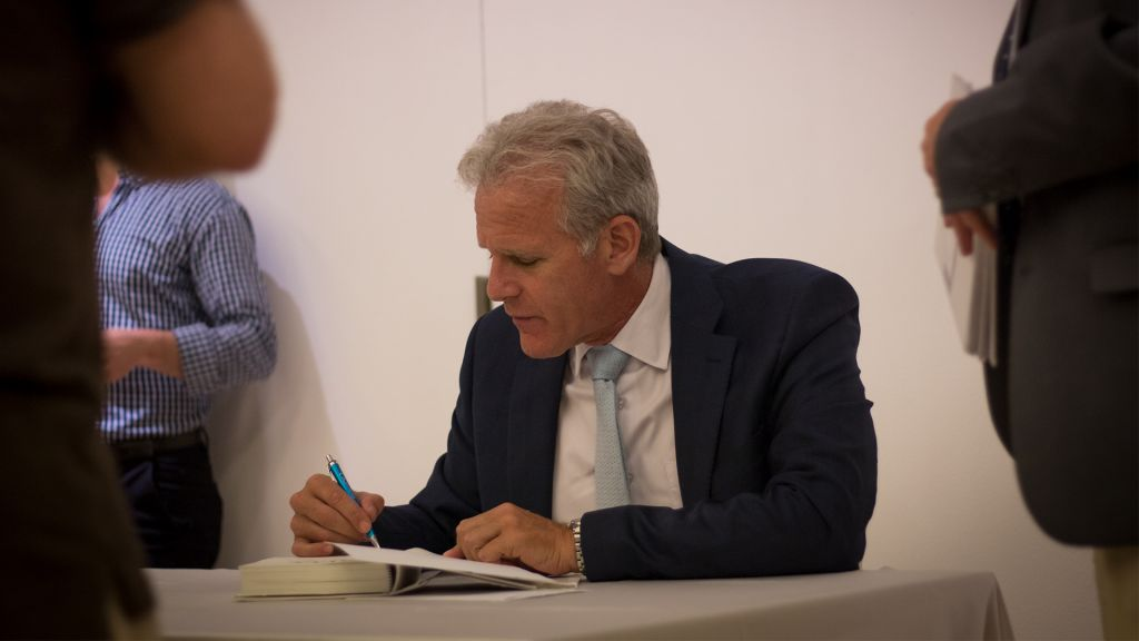 Michael Oren autographs books following a Times of Israel event in Jerusalem, May 28, 2017. (Luke Tress/Times of Israel)