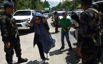Philippine policemen check evacuees from Marawi at a checkpoint by the entrance of Iligan City, on the southern Philippine island of Mindanao on May 24, 2017. /AFP PHOTO / TED ALJIBE