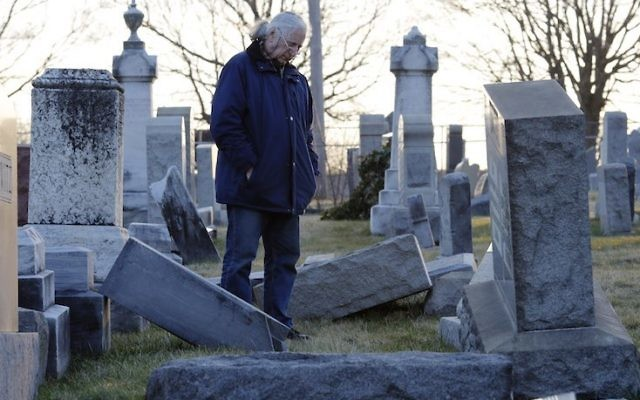 A man looks at fallen tombstones at the Jewish Mount Carmel Cemetery, February 26, 2017, in Philadelphia, PA.  (DOMINICK REUTER/AFP/Getty Images, via JTA)