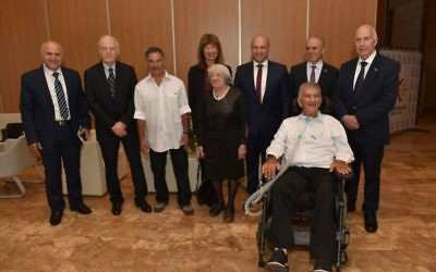 Eight of the nine winners of the 2017 Israel Prize pose at Jerusalem's International Convention Center on May 2, 20107. From left: Yosef Yarden, Arie Vardi, David Beeri, Nili Cohen (behind), Agnes Keleti, Naftali Bennett, Zvika Levy (in wheelchair), and Uri Shaked. Not shown: Yehuda Liebes and Malka Margalit. (Shlomi Amsalem)