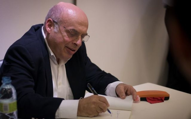 Natan Sharansky, chairman of the Jewish Agency, signs books at a Times of Israel event in Jerusalem, May 7, 2017. (Luke Tress/Times of Israel)