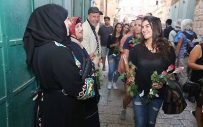 During a peace walk organized by Tag Meir a woman hands flowers to Arab shopkeepers in Jerusalem's Old City ahead of the Jerusalem Day flag parade, May 24, 2017. (Courtesy)