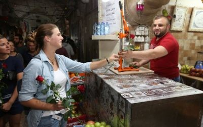 During a peace walk organized by Tag Meir, a woman hands a flower to an Arab shopkeeper in Jerusalem's Old City ahead of the Jerusalem Day flag parade, May 24, 2017. (Courtesy)