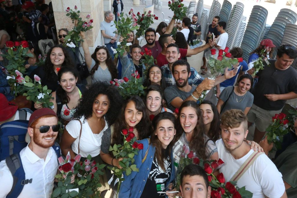 Peace activists take part in a Tag Meir peace march to hand out flowers to Arab shopkeepers in Jerusalem's Old City ahead of the Jerusalem Day flag parade, May 24, 2017. (Courtesy)