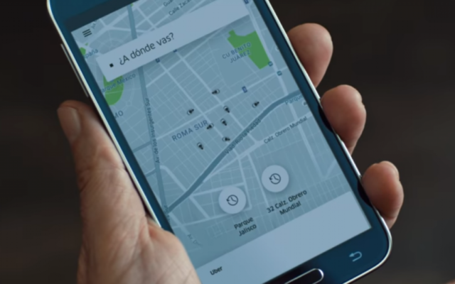 A passenger uses the Uber app to order a ride in the ride-sharing company's December 2016 ad. (Screen capture/YouTube)