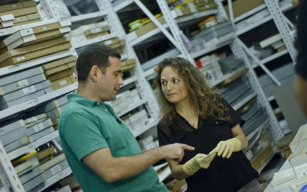 Dr. Erez Ben-Yosef and Dr. Naama Sukenik examining fragments of colored textiles recovered at Timna. (Yolli Schwartz, courtesy of the Israel Antiquities Authority)