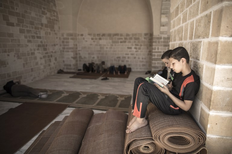 Palestinian children read copies of the Koran, Islam's holiest book, on the first day of fasting in the Muslim holy month of Ramadan, at the al-Omari mosque in Gaza City, on May 27, 2017. (AFP PHOTO / Mahmud Hams)