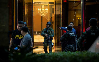 Philippines police officers come out from the Resorts World Hotel in Manila on June 2, 2017 following an assault. (Noel Celis/AFP)