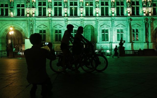 A picture taken on June 1, 2017, shows the City Hall of Paris illuminated in green following the announcement by US President Donald Trump that the United States will withdraw from the 2015 Paris accord and try to negotiate a new global deal on climate change. (AFP PHOTO / GEOFFROY VAN DER HASSELT)