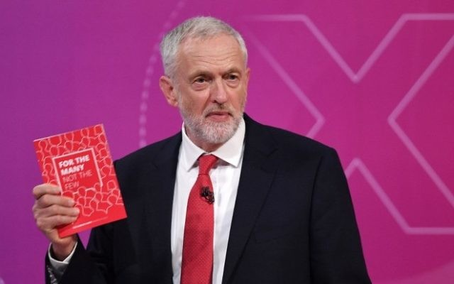 """Labour leader Jeremy Corbyn holds up the Labour Party manifesto as he takes part in """"The Question Time, Leaders Special"""" hosted byDavid Dimbleby in York in northern England on June 2, 2017, ahead of the upcoming general election. AFP/ Stefan Rousseau)"""