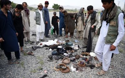Afghan men stand over the belongings of blast victims at the site of a series of explosions that targeted a funeral of a politician's son, who was killed during an anti-government protest a day earlier, at Badam Bagh in Kabul on June 3, 2017 ( AFP PHOTO / WAKIL KOHSAR)