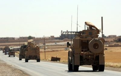 US-made armored vehicles are seen on a road near the northern Syrian village of Ain Issa on June 3, 2017. (AFP PHOTO / DELIL SOULEIMAN)