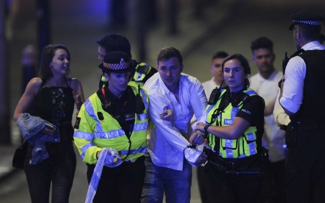 Police escort a member of public as they clear the scene of a terror attack on London Bridge in central London on June 3, 2017. (AFP PHOTO / DANIEL SORABJI)