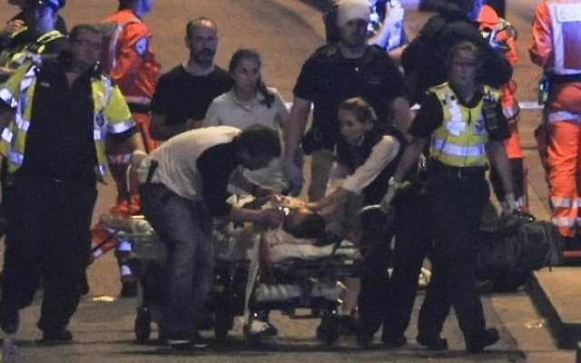 Police and members of the emergency services attend to victims of a terror attack on London Bridge in central London, June 3, 2017. (AFP/DANIEL SORABJI)