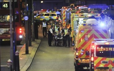 Police officers and members of the emergency services attend to a person injured in a terror attack on London Bridge in central London, June 3, 2017. (AFP/Daniel Sorabji)