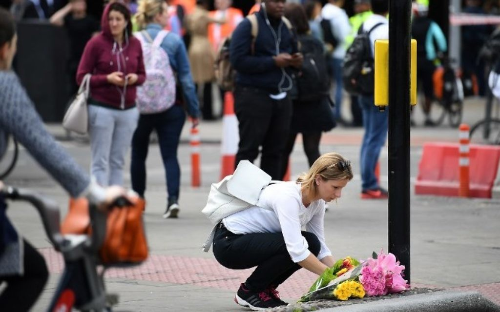 A woman lays a bouquet of flowers at a pedestrian crossing by Borough market in London on June 5, 2017. (AFP PHOTO / Justin TALLIS)