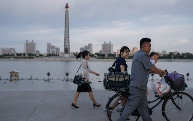 In a photo taken on June 4, 2017 a man pushes a child on a bicycle past the Juche tower and Taedong river in Pyongyang, North Korea (AFP Photo/Ed Jones)