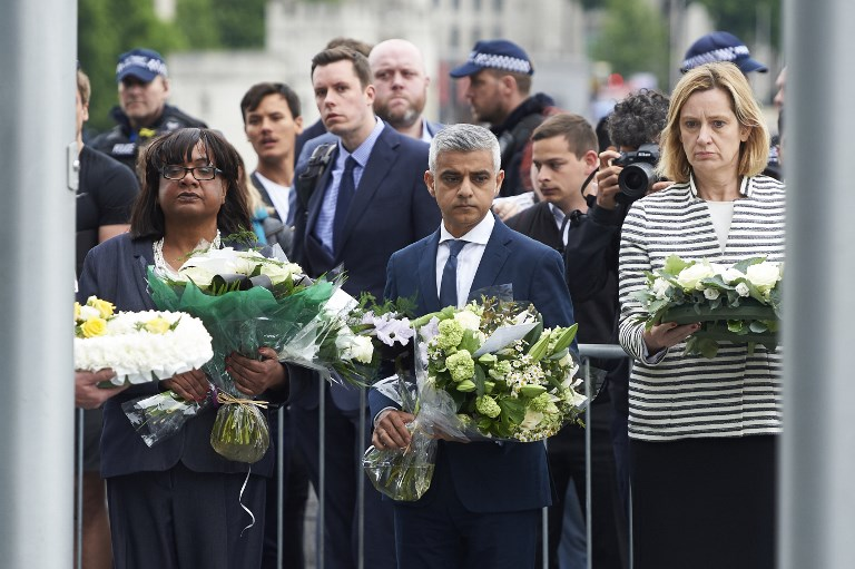 London Mayor Sadiq Khan (C), Home Secretary Amber Rudd (R) and Shadow Home Secretary Diane Abbott (L) hold flowers at Potters Fields Park in London on June 5, 2017, during a vigil to commemorate the victims of the terror attack on London Bridge and at Borough Market that killed seven people on June (AFP PHOTO / Niklas HALLE'N)
