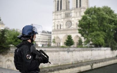 A French police officer holds a gun as he stands near the entrance of Notre Dame cathedral in Paris on June 6, 2017. (AFP Photo/Martin Bureau)