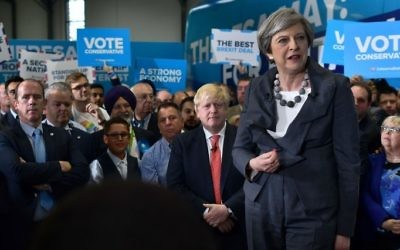 British Prime Minister Theresa May, right, is accompanied by Britain's Foreign Secretary Boris Johnson (2R) as she addresses supporters at a campaign event in Slough in south-east England on June 6, 2017. (AFP/Ben STANSALL)