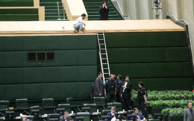 A picture taken on June 7, 2017 shows policemen deploying in the main hall of Iranian parliament to protect lawmakers during the attack which targeted the complex on June 7, 2017. (AFP/CHAVOSH HOMAVANDI)