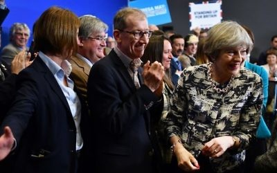 Britain's Prime Minister and leader of the Conservative Party Theresa May, right, and her husband Philip, center, after a general election campaign event in Norwich, east England, on June 7, 2017. (AFP Photo/Pool/Ben Stansall)