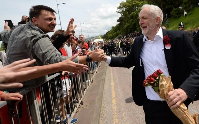 Britain's main opposition Labour Party leader Jeremy Corbyn greets supporters as he leaves after attending a campaign visit in Colwyn Bay, north Wales on June 7, 2017, on the eve of the general election. (AFP PHOTO / Oli SCARFF)
