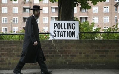 An ultra-Orthodox Jewish man walks past a polling station sign in northeast London,  June 8, 2017. (AFP/Daniel Leal-Olivas)