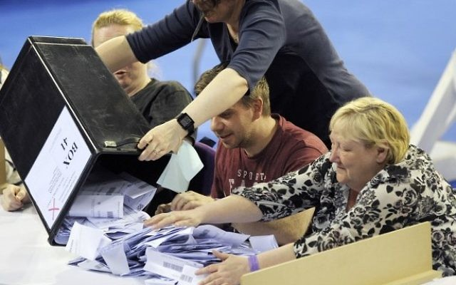 Staff members empty a ballot box at the main Glasgow counting centre in Emirates Arena in Glasgow, Scotland, on June 8, 2017, after the polls closed in Britain's general election. (AFP PHOTO / Andy Buchanan)