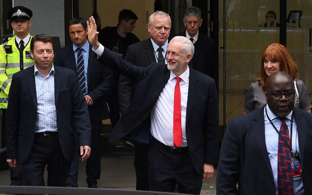 Britain's opposition Labour leader Jeremy Corbyn waves as he leaves the Labour Party headquarters in central London on June 9, 2017 after results in a snap general election show a hung parliament with Labour gains and the Conservative Party losing its majority. (AFP PHOTO / Paul ELLIS)