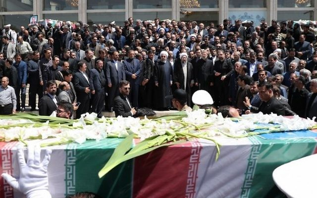 A handout picture provided by the Iranian Presidency on June 9, 2017 shows (C to R) Iran's President Hassan Rouhani, parliament speaker Ali Larijani and judiciary chief Sadeq Larijani standing among other officials the funeral of the victims of twin attacks in Tehran earlier in the week. (AFP/Iranian Presidency)