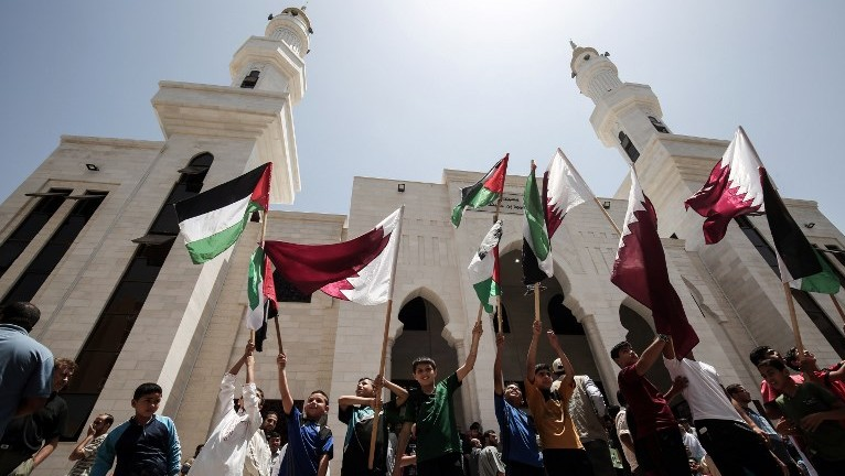 Palestinians rally in support of Qatar at a Qatari-funded housing project in the southern Gaza city of Khan Yunis on June 9, 2017. (AFP Photo/Said Khatib)