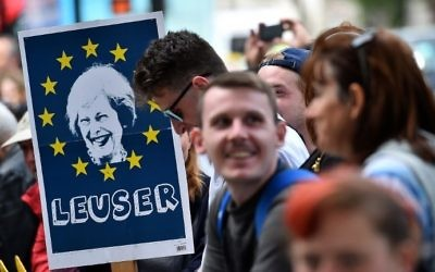 A demonstrator holds a placard depicting an image of Britain's Prime Minister Theresa May, surrounded by the stars of the EU flag and with the words 'Leuser,' as he stands outside the entrance to Downing Street, in central London on June 9, 2017, following the result of the general election. (AFP/Glyn Kirk)