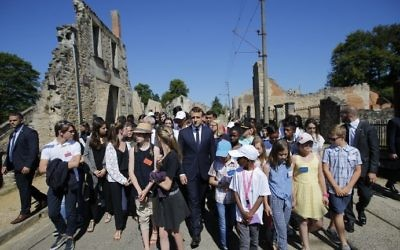 French President Emmanuel Macron (C) walks with children during a ceremony to commemorate the 73rd anniversary of the Oradour-sur-Glane massacre in the village of Oradour-sur-Glane on June 10, 2017. (AFP/Pool/Stephane Mahe)