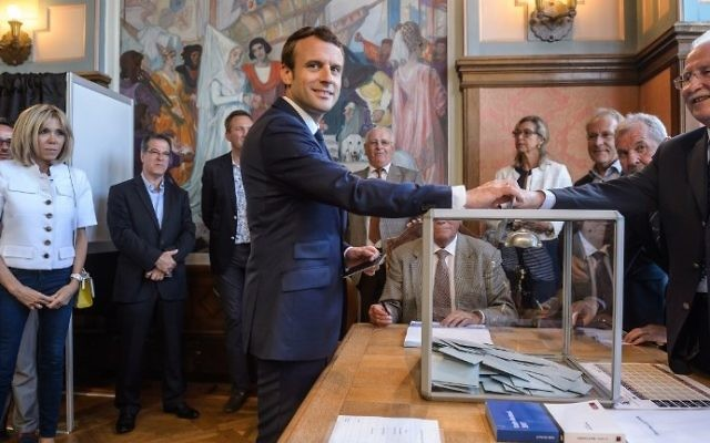 French President Emmanuel Macron (C) casts his ballot next to his wife Brigitte Macron (L) at a polling station during the first round of the French legislative elections in Le Touquet, on June 11, 2017.  (AFP PHOTO / POOL / Christophe Petit Tesson)