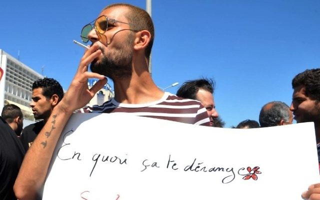 """A Tunisian protester smokes a cigarette and holds a placard reading in French """"Why is it bothering you? If you fast and I eat?"""" during a demonstration for the right to eat and smoke in public during the Muslim dawn-to-dusk fasting month of Ramadan, on June 11, 2017, in Tunis. (AFP/ Sofienne HAMDAOUI)"""